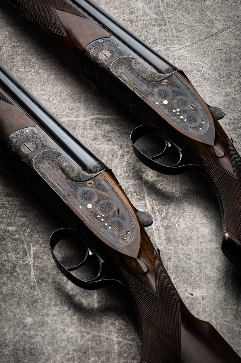 A pair of J Woodward over and under 12g guns